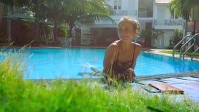 Nettes blondes Mädchen in den Bikiniresten im Pool, das auf Sperre sich lehnt stock footage