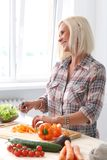 Nettes, blondes Mädchen an der Küche Lizenzfreie Stockfotos