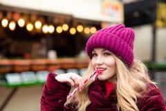 Nettes blondes Mädchen in der roten Strickmütze, die mit Zuckerstange a aufwirft Lizenzfreie Stockfotografie