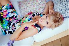 Nettes blondes Mädchen in einem hellen Kleid, das auf einem weißen Sofa liegt Lizenzfreies Stockbild