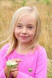 Nettes blondes Mädchen im Gras. Stockfotografie