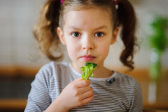Nettes blondes Mädchen isst frischen Brokkoli Lizenzfreie Stockbilder