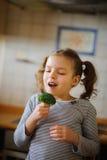 Nettes blondes Mädchen isst frischen Brokkoli Lizenzfreies Stockfoto