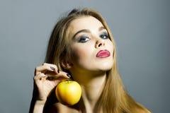 Nettes blondes Mädchen mit Apfel Lizenzfreie Stockfotografie