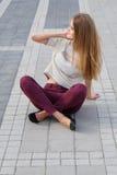 Nettes blondes Mädchen mit dem langen Haar, das auf dem Boden sitzt Lizenzfreie Stockfotografie