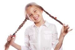 Nettes blondes Mädchen mit Zöpfen lächelnd auf weißem Hintergrund Lizenzfreie Stockbilder