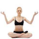 Nettes blondes Mädchen sitzen in der Yoga lotos asana Haltung Lizenzfreie Stockbilder