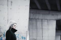 Nettes blondes Mädchen vor futuristischer Betonkonstruktion Lizenzfreie Stockfotografie