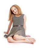 Nettes blondes Mädchenkleid, das auf dem Boden sitzt Stockbilder
