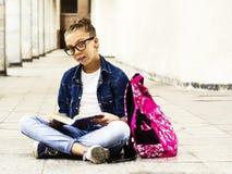 Nettes blondes Mädchenschulmädchen, das ein Buch beim Sitzen nahe Schule liest Ausbildung Stockfoto
