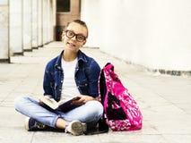Nettes blondes Mädchenschulmädchen, das ein Buch beim Sitzen nahe Schule liest Ausbildung Stockfotos