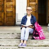 Nettes blondes Mädchenschulmädchen, das ein Buch beim Sitzen nahe Schule liest Ausbildung Lizenzfreies Stockbild