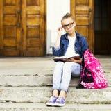 Nettes blondes Mädchenschulmädchen, das ein Buch beim Sitzen nahe Schule liest Ausbildung Lizenzfreie Stockfotos