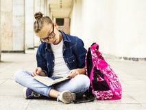 Nettes blondes Mädchenschulmädchen, das ein Buch beim Sitzen nahe Schule liest Ausbildung Stockfotografie