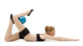 Nettes blondes Mädchentraining mit der blauen Kugel getrennt Lizenzfreies Stockbild