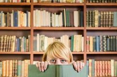 Nettes blondes Mädchen, das hinter einem Buch sich versteckt Lizenzfreie Stockfotografie