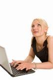 Nettes blondes Schreiben auf ihrem Laptop Lizenzfreie Stockbilder