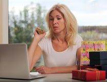 Nettes blondes unter Verwendung eines Laptops Stockbild