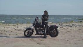 Nettes brunette kaukasisches Mädchen in der schwarzen ledernen Kleidung, die nahe dem Motorrad am Strand des Meeres steht liebhab stock video