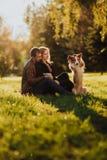Nettes cuple mit Hund border collie auf grünem Feld im Park unter Baum im Sonnenschein stockfotografie