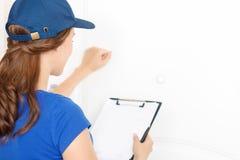 Nettes deliverywoman, das nahe Tür steht Stockbilder