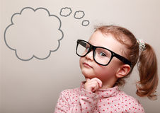 Nettes denkendes Kindermädchen in den Gläsern mit leerer Blase Stockfotografie