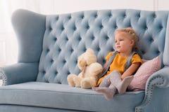 Nettes durchdachtes Mädchen, das nahe ihrem Teddybären sitzt Stockfotografie