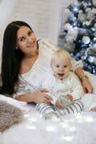 Nettes einjähriges Baby und seine schöne Mutter, die in neuem aufwirft Lizenzfreies Stockfoto