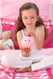Nettes Einsparunggeld des kleinen Mädchens in einem piggybank Lizenzfreies Stockbild