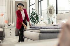 Nettes elegantes gealtertes missis, welches die Bettqualität im Speicher überprüft stockfotos