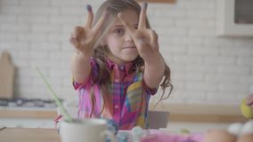 Nettes emotionales kleines M?dchen mit dem langen Haar, das zu den Kamerah?nden in der blauen Farbe, Grimassen machend in der K?c stock video footage