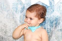 Nettes entzückendes Baby mit einem Finger in seinem Mund Stockfoto
