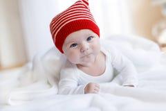 Nettes entzückendes Babykind mit Weihnachtswinterkappe auf weißem Hintergrund Glückliches Baby oder Junge, die lächeln und betrac lizenzfreies stockbild