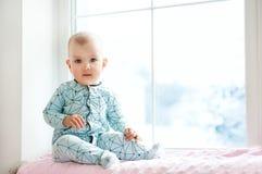 Nettes entzückendes kleines Baby, das durch Fenster sitzt und zum Nocken schaut Kind genießen Schneefälle Frohe Feiertage und Wei lizenzfreies stockbild