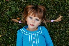 nettes entzückendes kleines rothaariges kaukasisches Mädchenkind im blauen Kleid, das draußen im Feldwiesenpark liegt Stockfoto