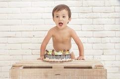Nettes entzückendes Kleinkind mit seinem Kuchen Lizenzfreie Stockfotos