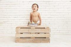 Nettes entzückendes Kleinkind mit seinem Kuchen Stockfotos