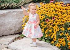 Nettes entzückendes weißes kaukasisches Babykind im weißen Kleid, das unter gelben Blumen draußen im Gartenpark steht Lizenzfreie Stockfotografie