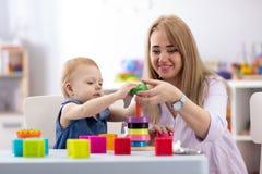 Nettes Frauen- und Kinderspiel zusammen Innen lizenzfreie stockfotografie