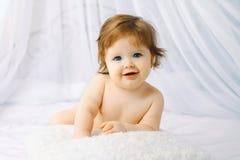 Nettes frohes Baby auf dem Betthaus Stockbilder