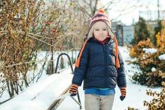 Nettes Gehen des kleinen Jungen im Freien in der Winterzeit Kind, das mit Schnee spielt Lizenzfreies Stockbild
