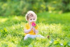 Nettes gelocktes Baby, das Wassermelonensüßigkeit im sonnigen Park isst Stockbild
