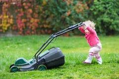Nettes gelocktes Baby mit Rasenmäher im Garten lizenzfreie stockfotografie