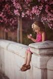 Nettes gelocktes blondes Kindermädchen in der rosa Ausstattung, die auf der Wand unter blühendem Baum sitzt Stockbild