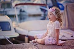 Nettes gelocktes blondes Kindermädchen im rosa Rock, der in den Docks sitzt Lizenzfreie Stockfotografie