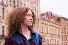 Nettes gelocktes junges Mädchen auf dem Hintergrund der Stadt lizenzfreies stockbild