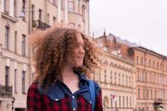 Nettes gelocktes junges Mädchen auf dem Hintergrund der Stadt stockfotos