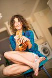 Nettes gelocktes Mädchen, das ein Brötchen sitzt auf einem Stuhl in der Küche isst lizenzfreie stockbilder