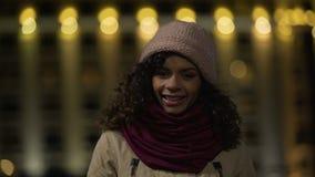 Nettes gelocktes zufälliges Mädchen, das aufwirft und herzlichst an der Kamera, glückliche Dame lächelt stock footage