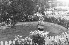 Nettes glückliches Baby, das mit Ball auf grünem Gras spielt Stockbilder
